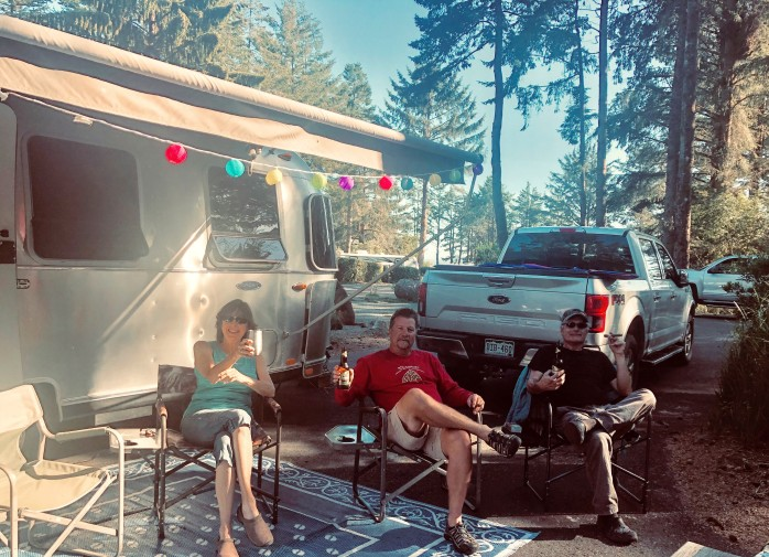 people drinking beer by a camper