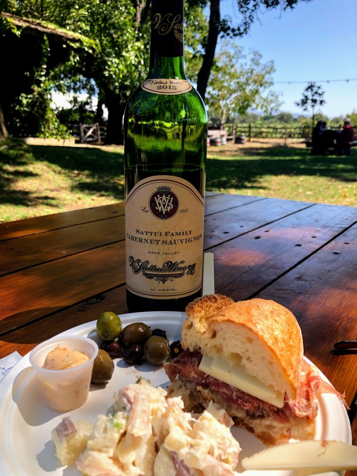 bottle of wine with sandwich and potato salad