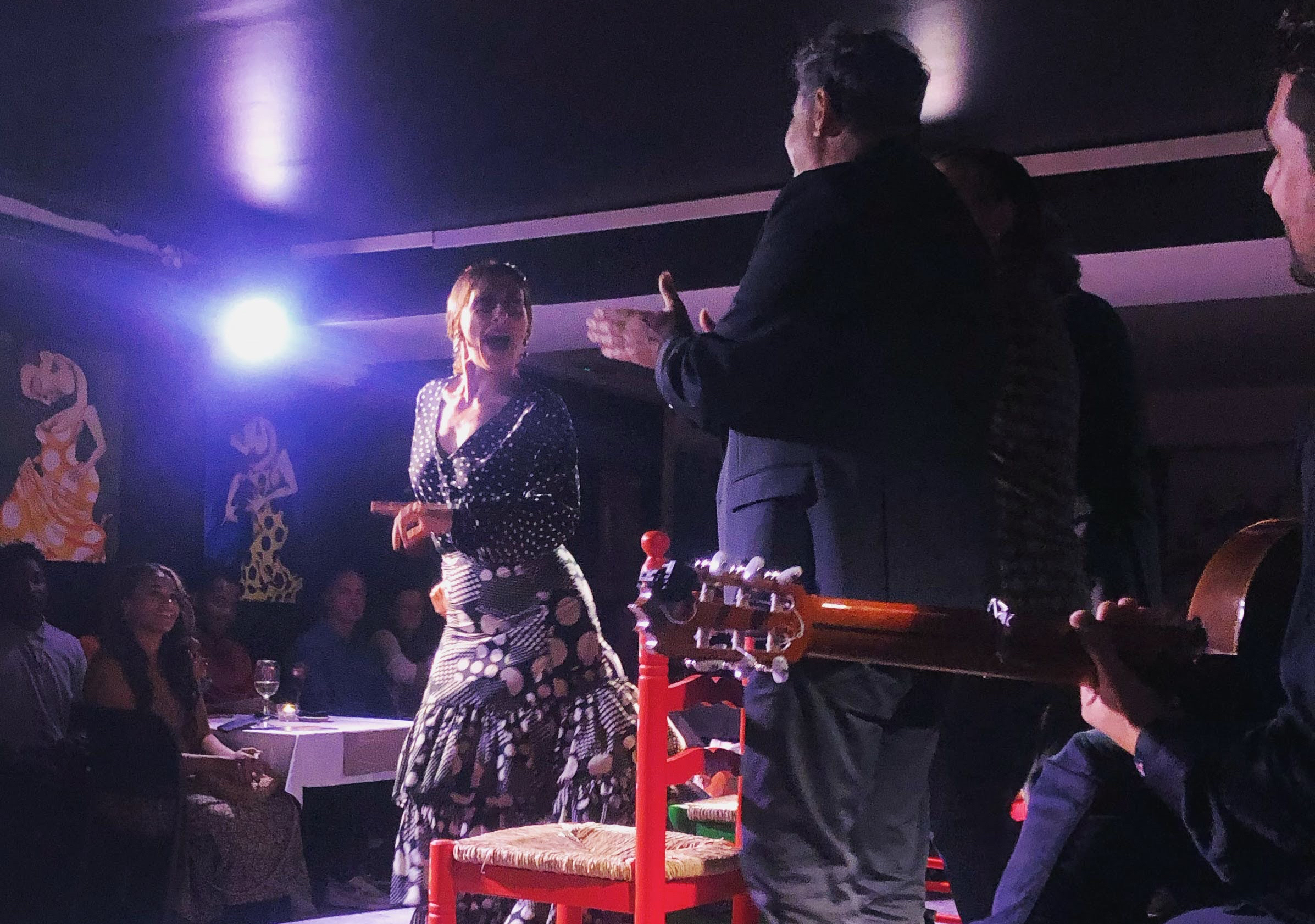 woman dancing flamenco with men on stage clapping