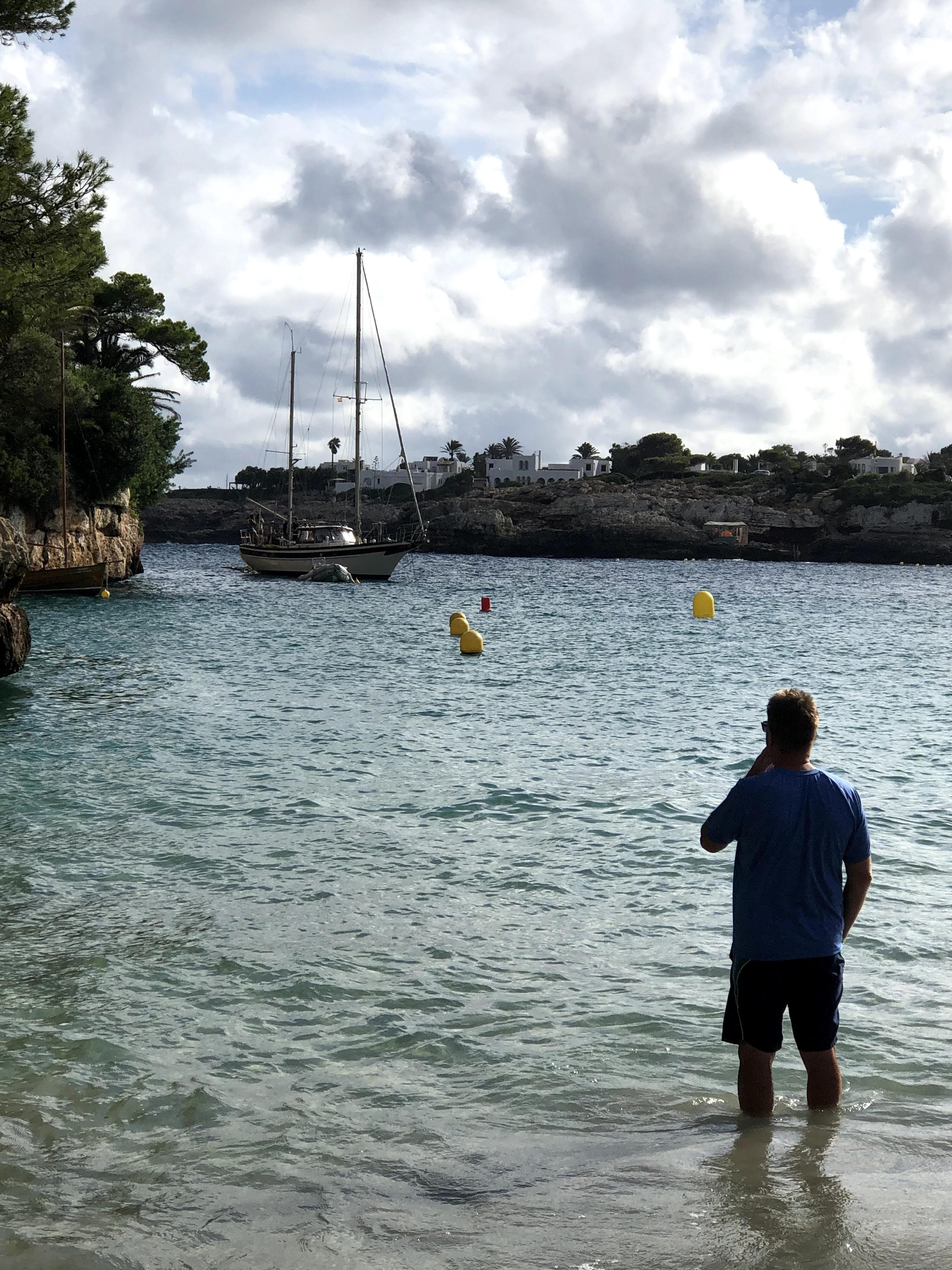 man on beach looking at sailboat